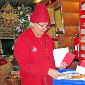 Postitonttu Auli Sihvo selailee kirjeitä Joulupukin pääpostissa maaliskuussa 2017. Taustalla joulukuusi, himmeli ja lahjapaketteja.