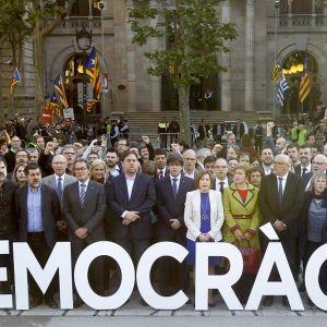 Valkoiset jättikirjaimet maassa, joissa lukee democrària. Takana seisoo joukko ihmisiä riveissä.