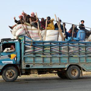 Siviiliasukkaat pakenevat Raqqan kaupungista.
