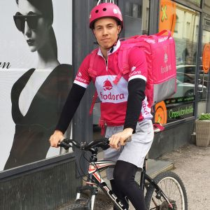 Ruokalähettifrima Foodoran kuljettaja poseeraa polkupyörän päällä vaaleanpunaisessa työasussa ja kypärässä