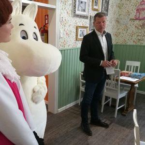 Eriskummallinen kahvila on Muumimaailman uusin kohde Naantalissa. Toimitusjohtaja Tomi Lohikoskea kuuntelevat Mymmeli ja Muumipeikko.