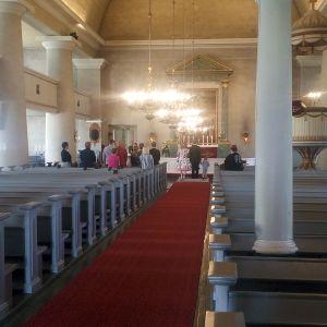 Pariskunta vihitään Keminmaan uudessa kirkossa, häävieraat seisovat.