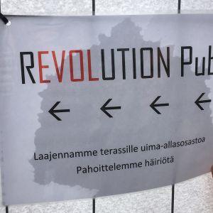 Kyltti, jossa Revolution mainostaa laajentavansa terassille uima-allasosastoa.