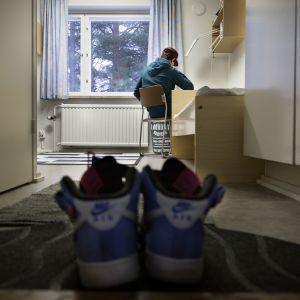 Alaikäinen turvapaikanhakija tekee läksyjä huoneessaan.
