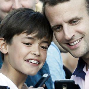 Emmanuel Macron poseeraa lapsen kanssa.