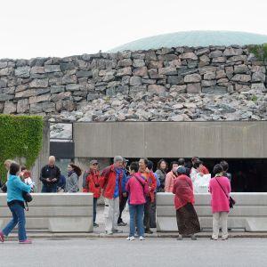 Turisteja ja betoniesteitä Temppeliaukion kirkon edustalla tiistaina 20. kesäkuuta