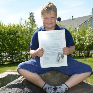 Niilas Keränen istuu kivellä kehystetty presidentin kirje sylissään.