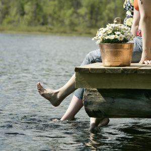 Lomalaisia istuu laiturin päässä jalat vedessä.