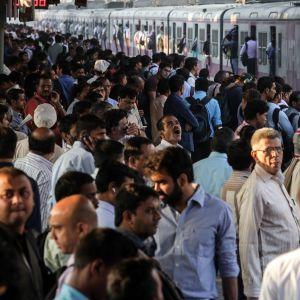 Intialaiset odottavat junaa täpötäydellä asemalla Mumbaissa.