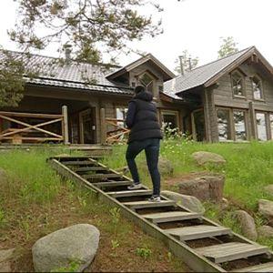 Nainen nousee mökin portaita