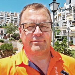 Perussuomalaisten Lapin piirin puheenjohtaja Matti Torvinen poseeraa aurinkoisissa maisemissa lukuisten loma-asuntojen ja kerrostalojen edessä.