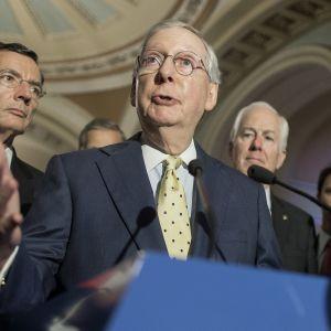 Senaatin republikaanijohtaja Mitch McConnell puhujapöntön takana. Vieressä muita ihmisiä.