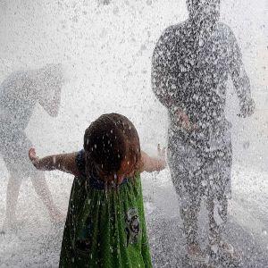 Ihmiset käyvät suihkulähteessä vilvoittelemassa kuumana päivänä.