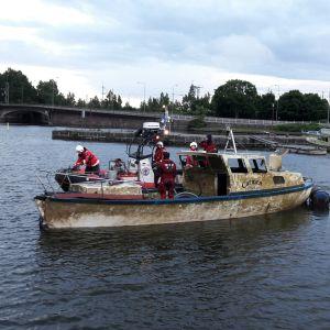 Meripelastajat ohjaavat meren pohjasta nostettua venettä rantaan