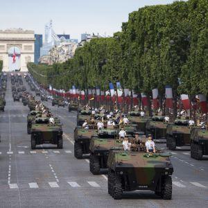 Ranskalaisjoukkoja ja panssariajoneuvoja kadulla. Taustalla riemukaari.