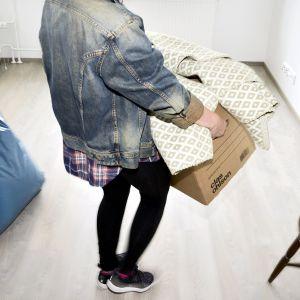 Nainen kantaa muuttolaatikkoa.
