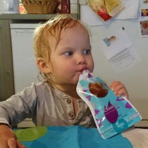 Pieni poika syö smoothie pussista