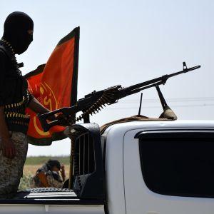 Taistelija seisoo avopakettiauton lavalla auton ohjaamon kuomuun kiinnitetyn konekiväärin takana. Taistelijalla on hiihtonaamio. Hänen vierellään heiluu punainen lippu.