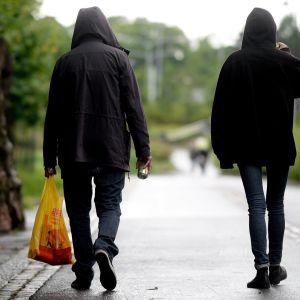 Nuoret kävelevät kadulla ja juovat olutta.