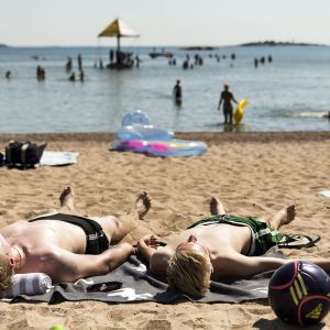 Ihmiset ottavat aurinkoa rannalla.