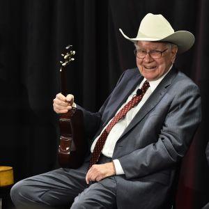 Warren Buffett istuu ukulele kädessään ja stetson päässään valmiina vastaamaan ylesiön kysymyksiin Teksasissa järjestetyssä hyväntekeväisyystapahtumassa 2015.