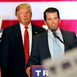 Donald Trump seisoo taustalla, kun hänen poikansa puhuu mikrofoniin. Vanhemmalla Trumpilla on musta puku ja punainen valkoraidallinen kravatti. Nuoremmalla Trumpilla on harmaa puku ja vaaleansininen pilkullinen kravatti. Taustalla näkyy Yhdysvaltain lipun värejä.