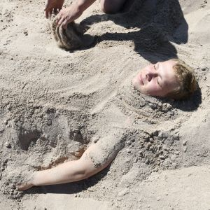 Mies kaivettuna rantahiekkaan.