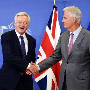 Brittien brexit-neuvottelija David Davis ja EU-neuvottelija Michel Barnier kättelevät.
