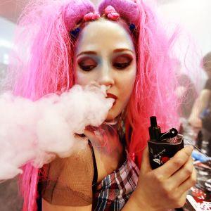 Nuori, vaaleanpunaiseen perukkiin pukeutunut nainen polttaa sähkötupakkaa.