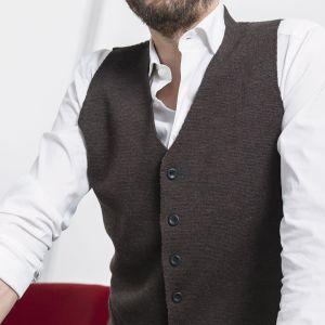 Mies paitapusero ja liivi päällä.