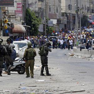 Palestiinalaiset osoittavat mieltä kadulla. Israelilaiset sotilaat osoittavat mielenosoittajia aseilla.