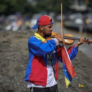 Viulisti soittaa kadulla, ja häen jousessa on kiinni Venezuelan lippu.