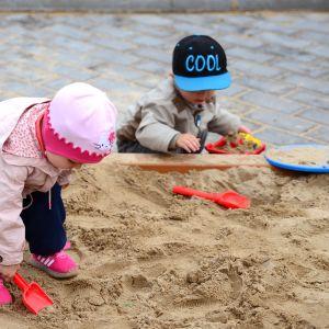 Kaksi lasta leikkii leikkipuiston hiekkalaatikolla.