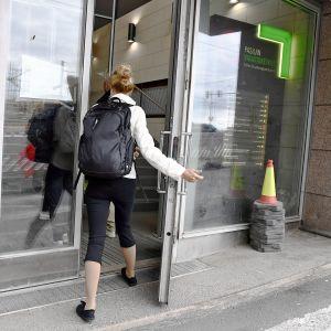 Nainen menee ovesta sisään Pasilan Virastokeskukseen.