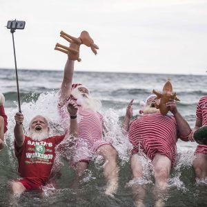 Joulupukkipukuiset poseeraavat meressä