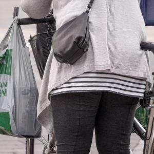 muovikassi naisen polkupyörän ohjaustangossa