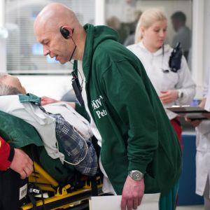Sairaanhoitaja puhuttelee iäkästä potilasta.