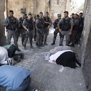 Muslimeja rukoilemassa. Israelin poliiseja katsomassa vieressä.