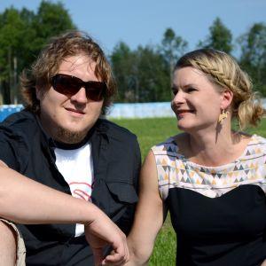 Matti ja Helena Poukkanen istuvat nurmikolla.