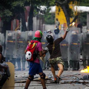 Mielenosoittajat taistelevat kadulla Venezuelan turvallisuusjoukkoja vastaan. Protestoija heittää palavaa esinettä hyvin suojautuneiden turvallisuusjoukkojen sekaan.