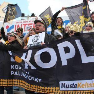 Kouvolan Pallonlyöjien faniryhmä pesäpallokatsomossa, pitelevät banderollia ja heiluttaat lippuja