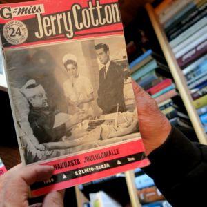 Jerry Cottonin numero 24 miehen käsissä, pöydällä lisää Cotton-lehtiä