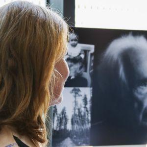 Leena Louhivaara katsoo valokuvaa näyttelyssä