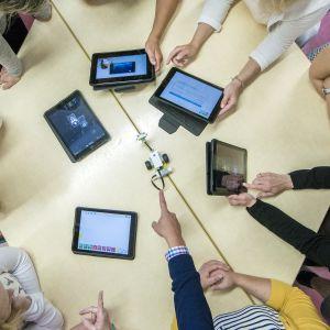 Opettajat opettelevat ohjelmoimaan pöydän ääressä.