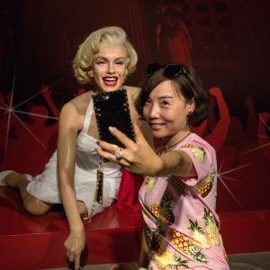 Virailija ottamassa selfietä Marilyn Monroe -nuken kanssa Madame Tussauds -vahakabinetissa Pekingissä, Kiinassa 11. elokuuta.