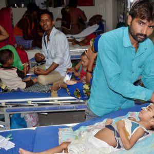 Perheenjäsenet hoitivat lapsiaan Baba Raghav Dasin sairaalassa Gorakhpurissa, Intiassa 12. elokuuta.