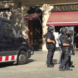Aseistautuneet poliisit partioivat tapahtumapaikan läheisyydessä.