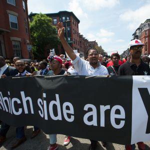 """Kuvassa mielenosoittajat kantavat lakanaa, jossa lukee """"Kummalla puolella olet"""""""
