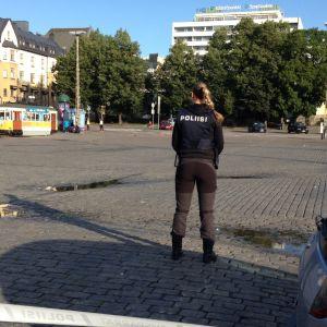 Poliisiviranomainen seisoo Turun kauppatorilla.