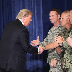 Trump kättelee rivissä seisovia sotilasjohtajia.